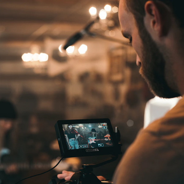 A man holding a video camera filming a band play