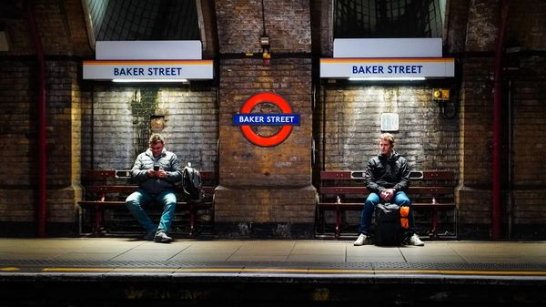 Two people sitting on the Baker Street subway station in London