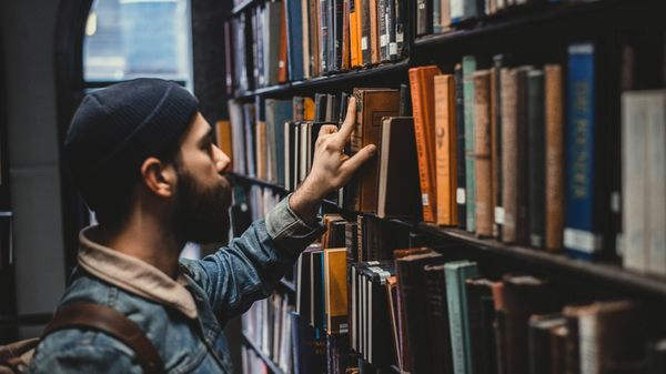 Man looking through books in a library