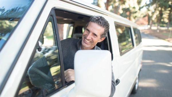 A dad driving up in his mini-van smiling.