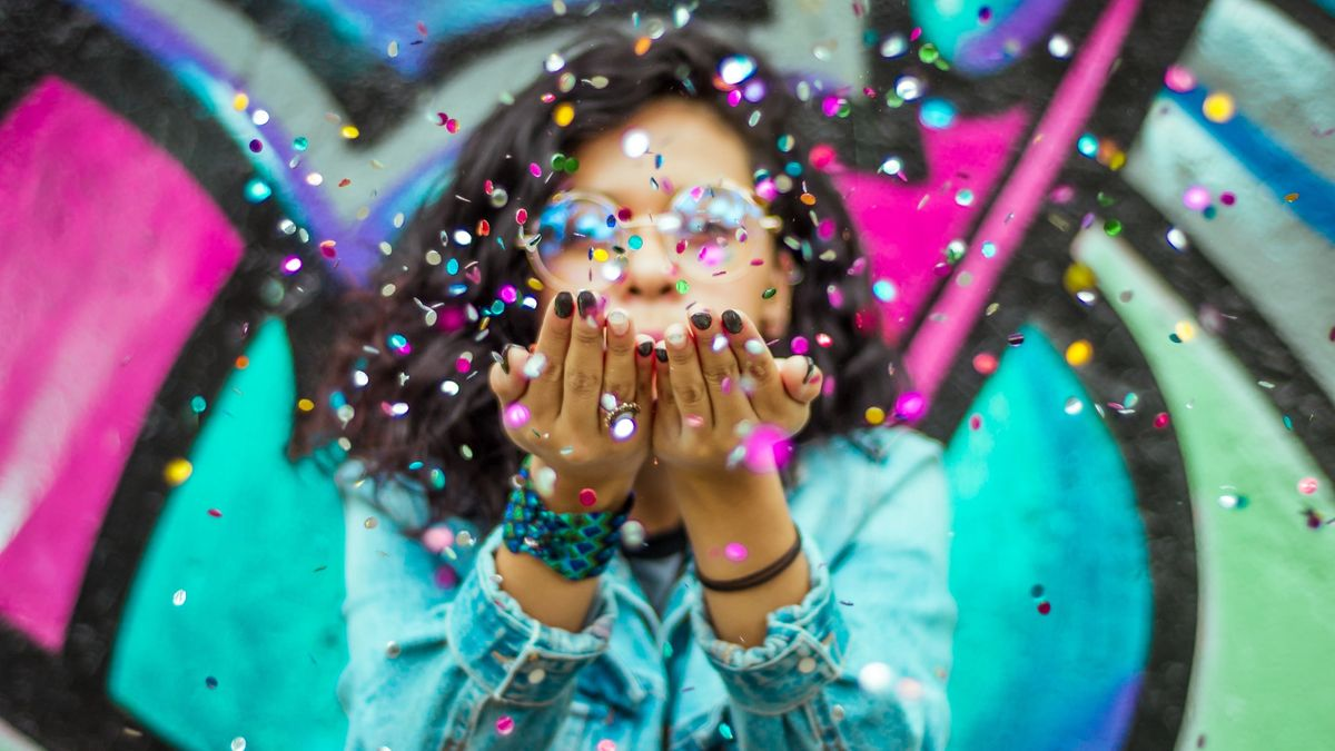 A woman blowing confetti in the air