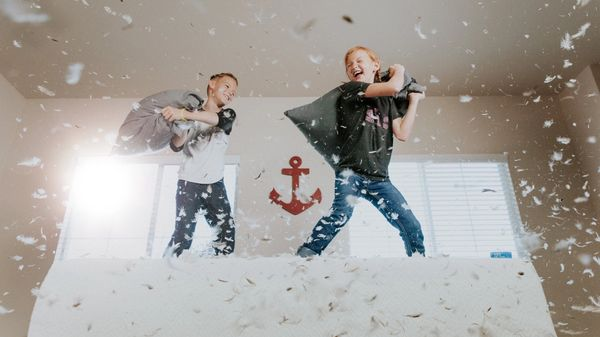 Two kids in a pillow fight