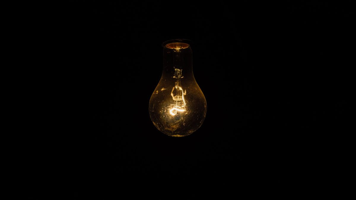 A black room with a dimly lit old school light bulb