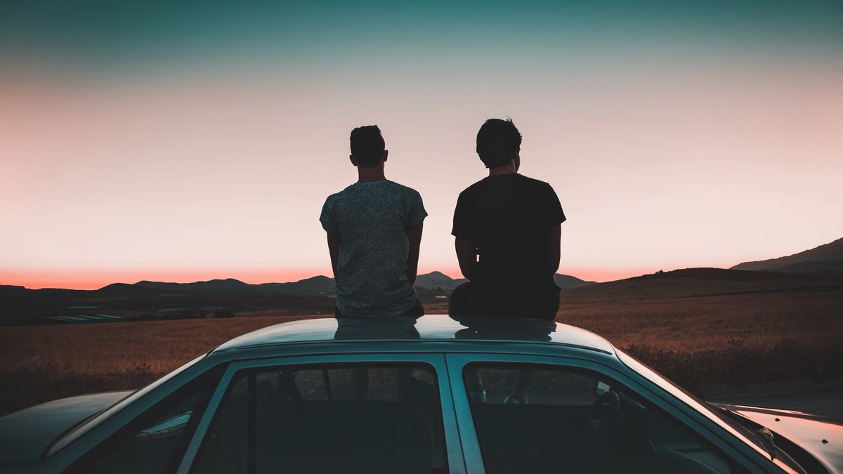 Two people sitting on top of a car roof, watching the sunset