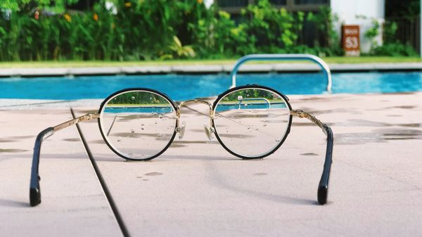 A pair of glasses next to a pool