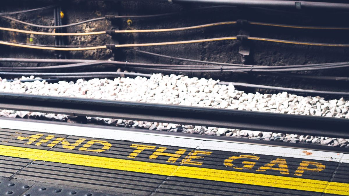 """A photo of the edge of a train platform, with the words """"mind the gap"""" painted on in bright yellow"""