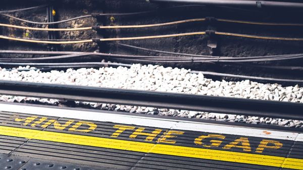 "A photo of the edge of a train platform, with the words ""mind the gap"" painted on in bright yellow"