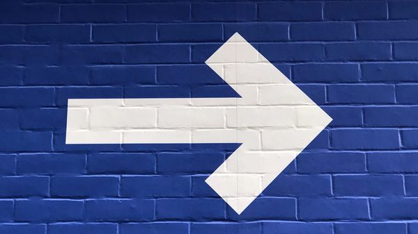 An arrow pointing to the right on a brick wall
