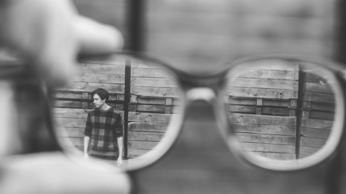 A man standing next to a wall, seen through some glasses from far away