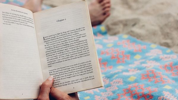 Person reading book on the beach