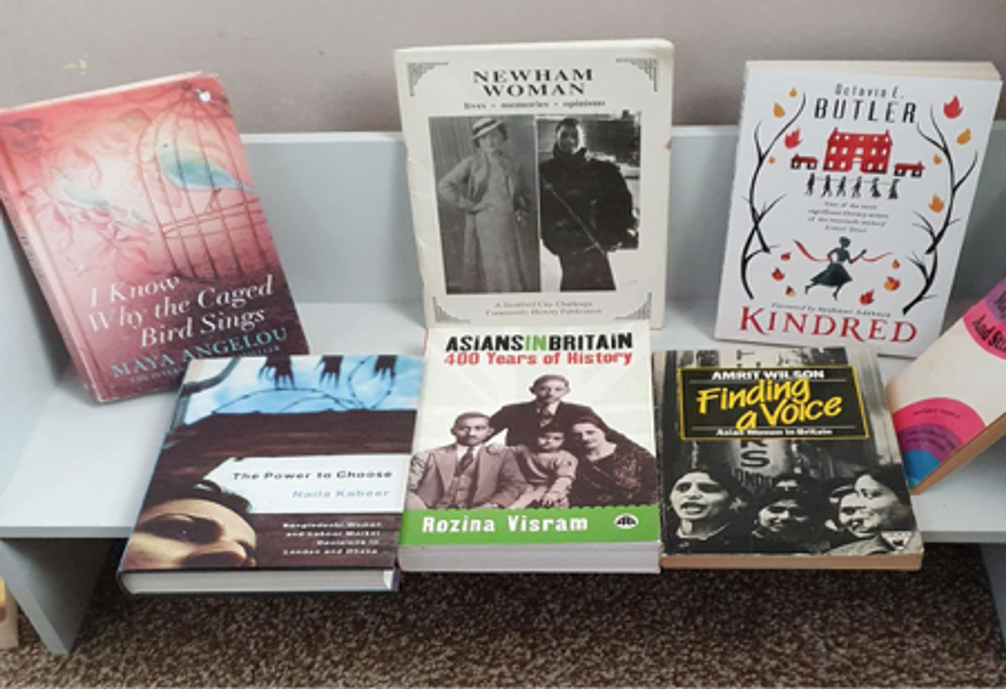 Selection of books by women authors on a freestanding shelf