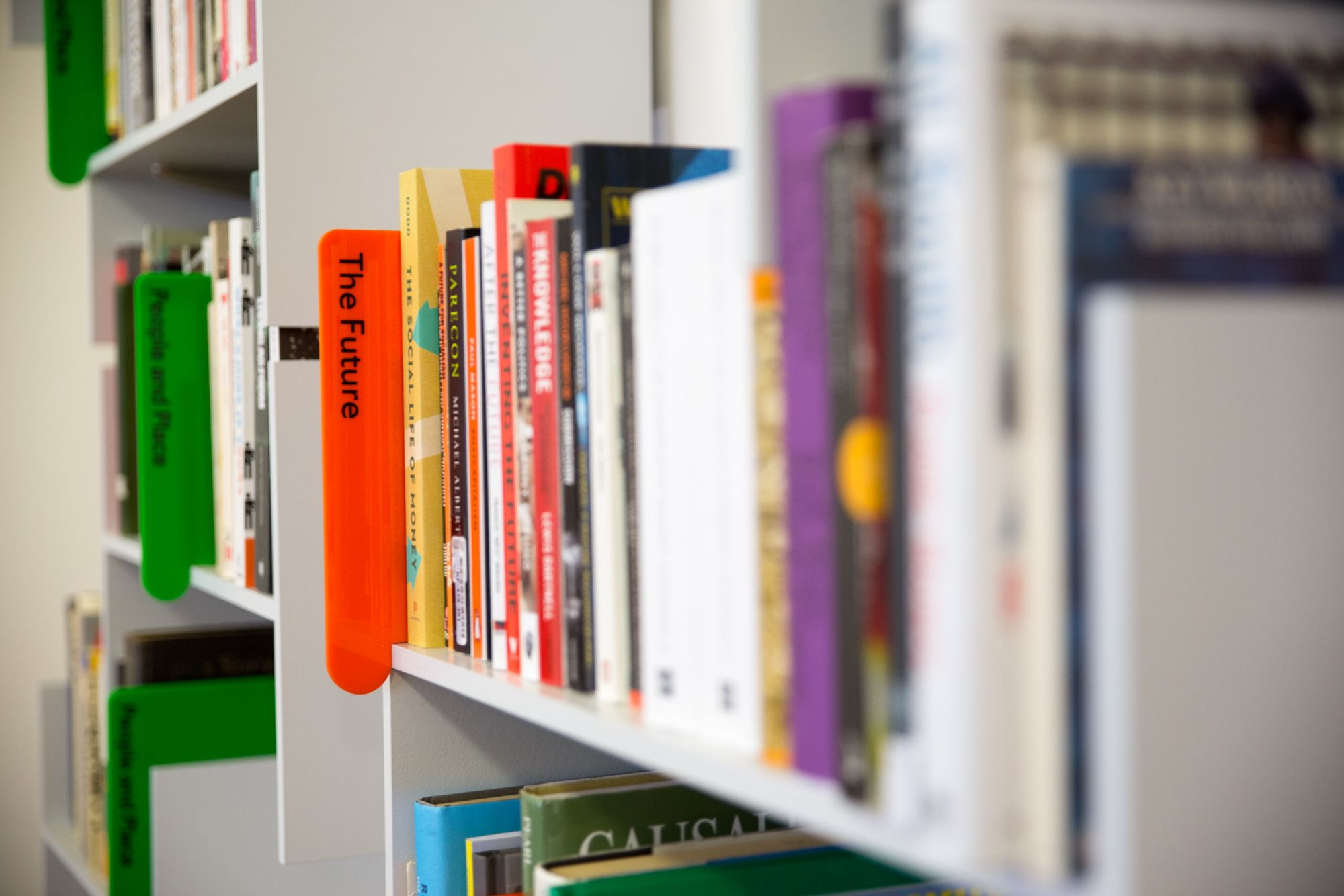 Wall mounted bookshelves full of books, viewed side-on, and several book dividers in view. The nearer one is orange and says The Future.