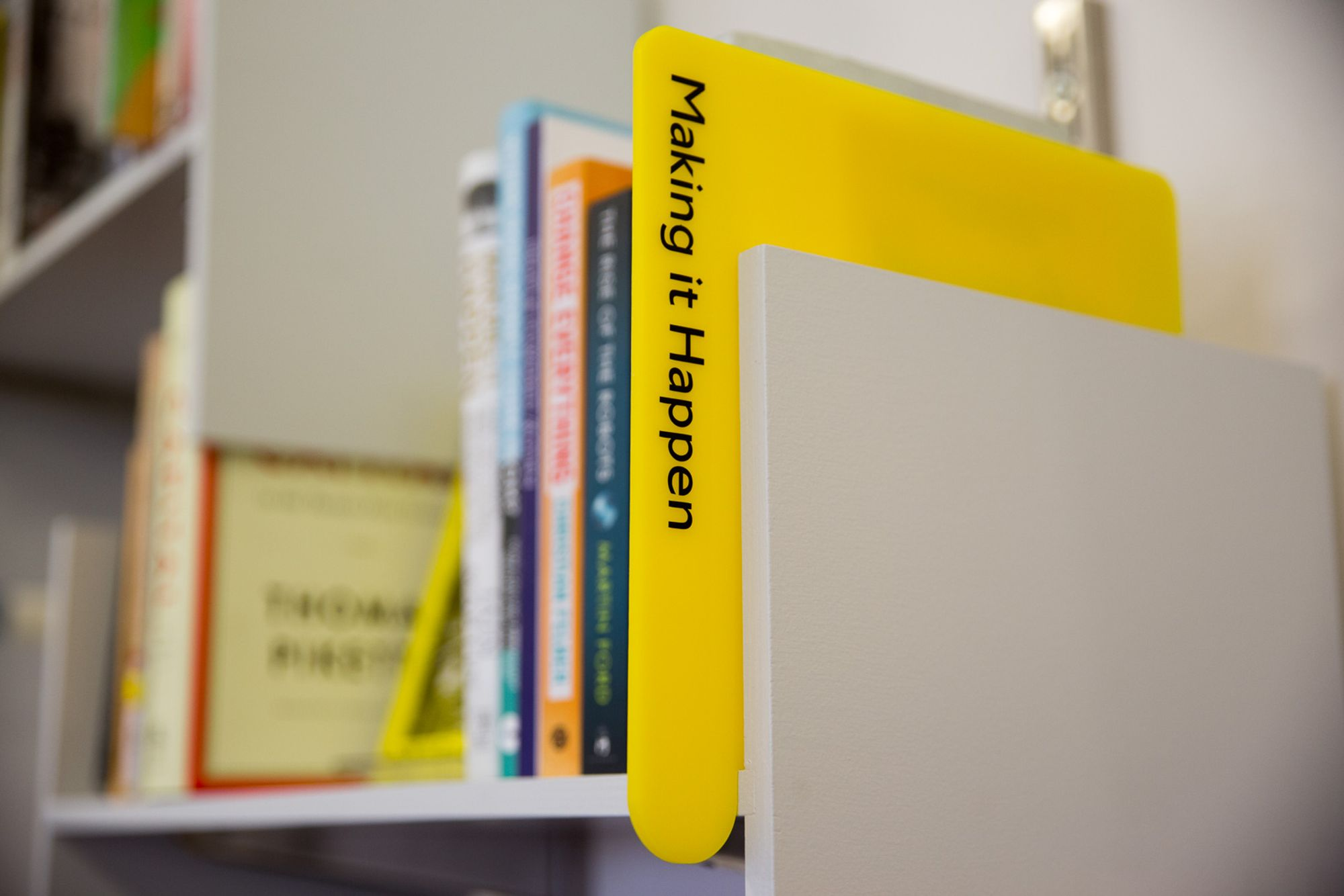 A grey bookshelf with a yellow divider with the words 'Making it Happen' and books in the background on the shelves, blurred out