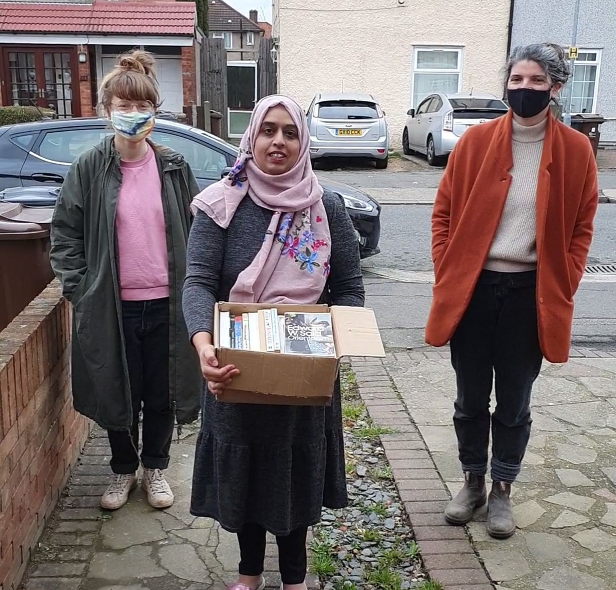 Farzana holding a box of books with Ruth and Amy standing either side
