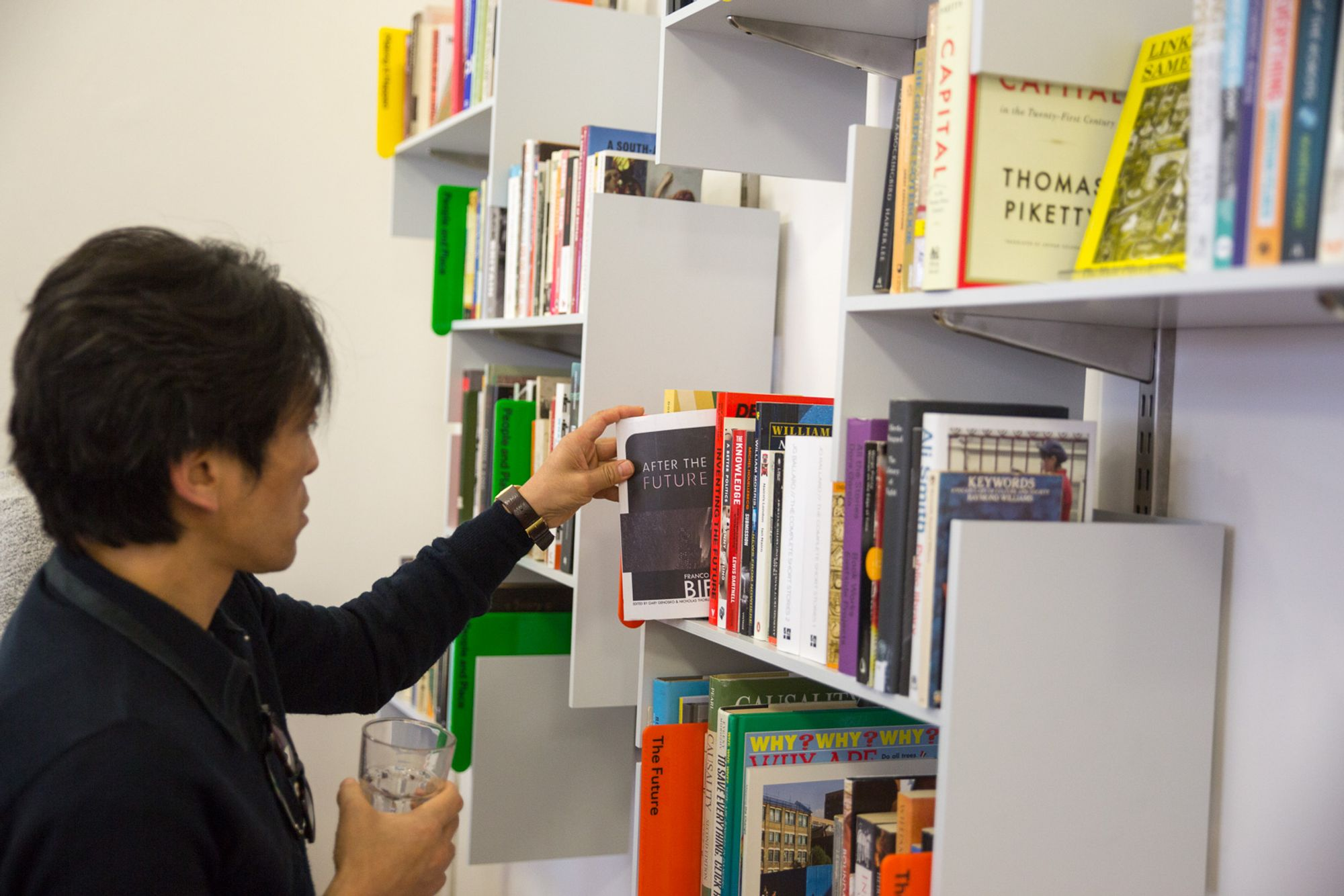 On the right, grey wallmounted shelves full of books. On the left, a man with dark hair and shirt, holding a glass and browsing the books