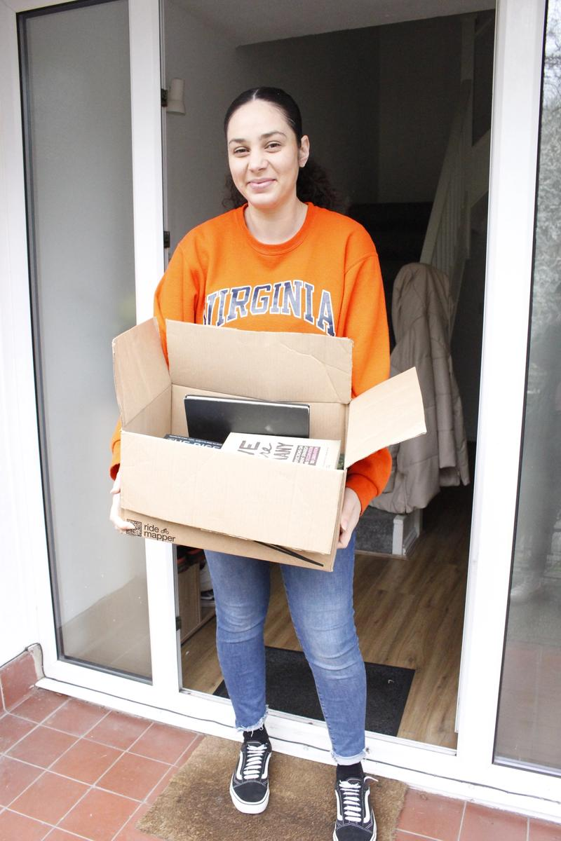Joelle David standing on her doorstep with a box of books