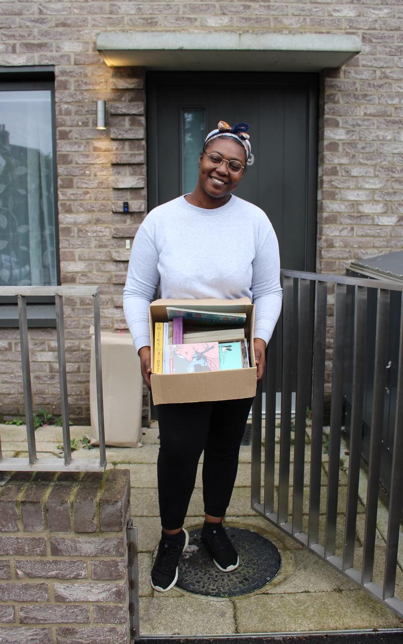Gail Egbeson standing outside on her doorstep holding a box of books