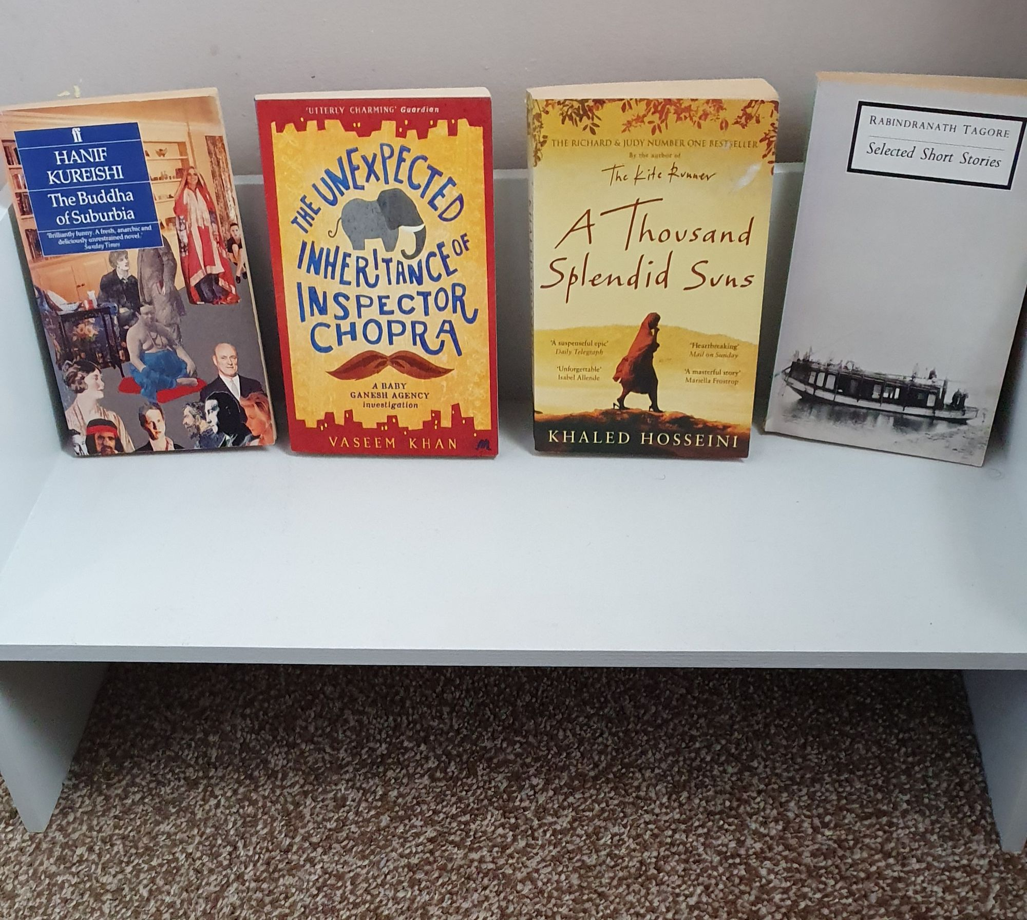 Selection of books by male authors on a free standing shelf