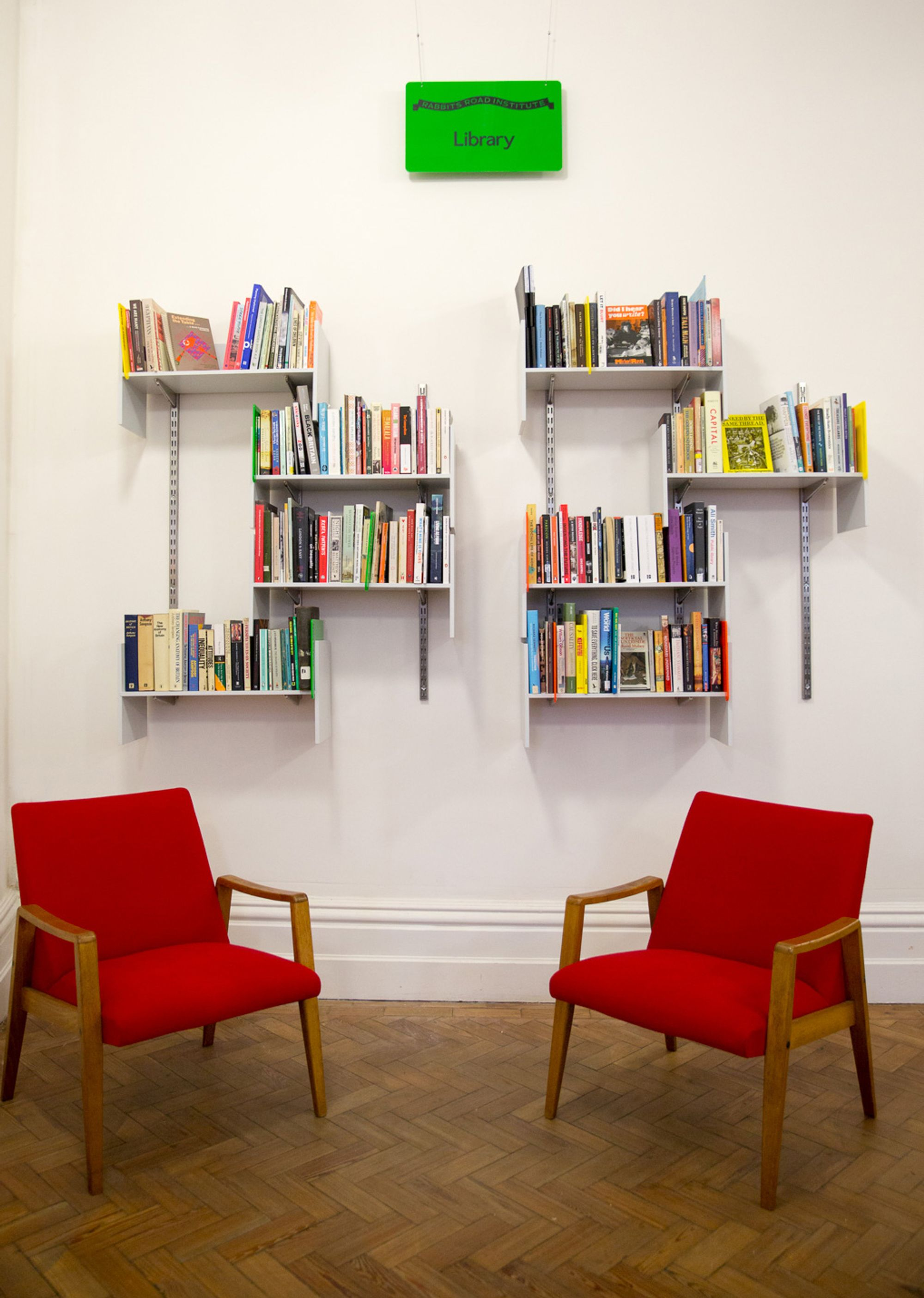 Eight wall mounted shelves full of books on a white wall; a green sign with the word 'Library' hangs above; in the foreground, two red midcentury lounge chairs.