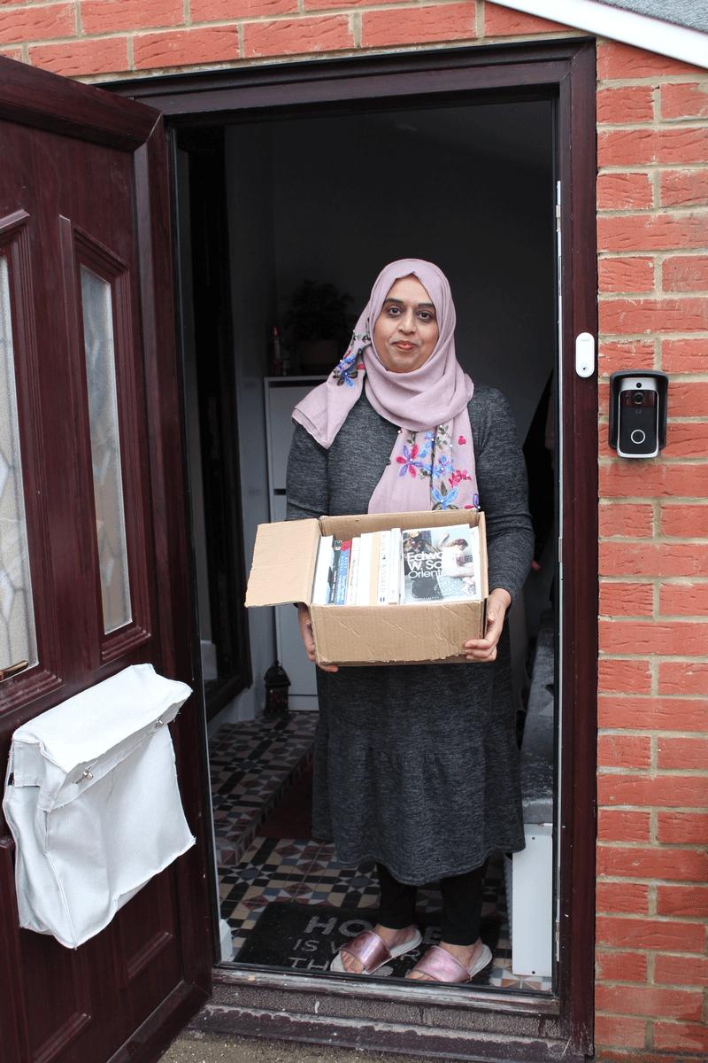Farzana on her doorstep holding a box of books