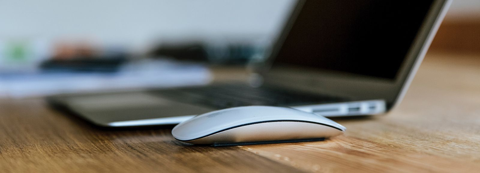 MacBook Air and Apple Magic Mouse on brown wooden table photo