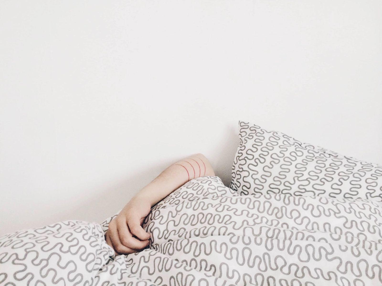 Person lazing under quilt blanket.