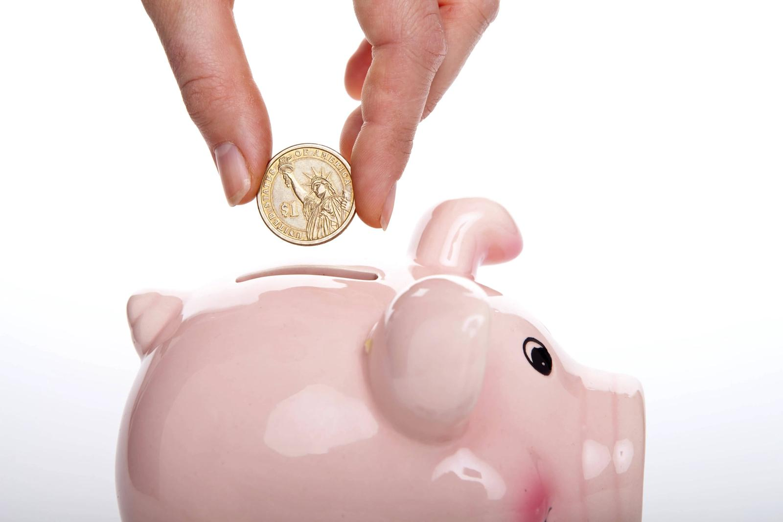Single coin being put into pink piggy bank.