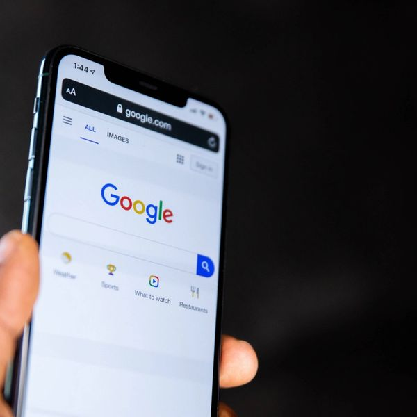 Person holding black Android smartphone with Google search page on screen.