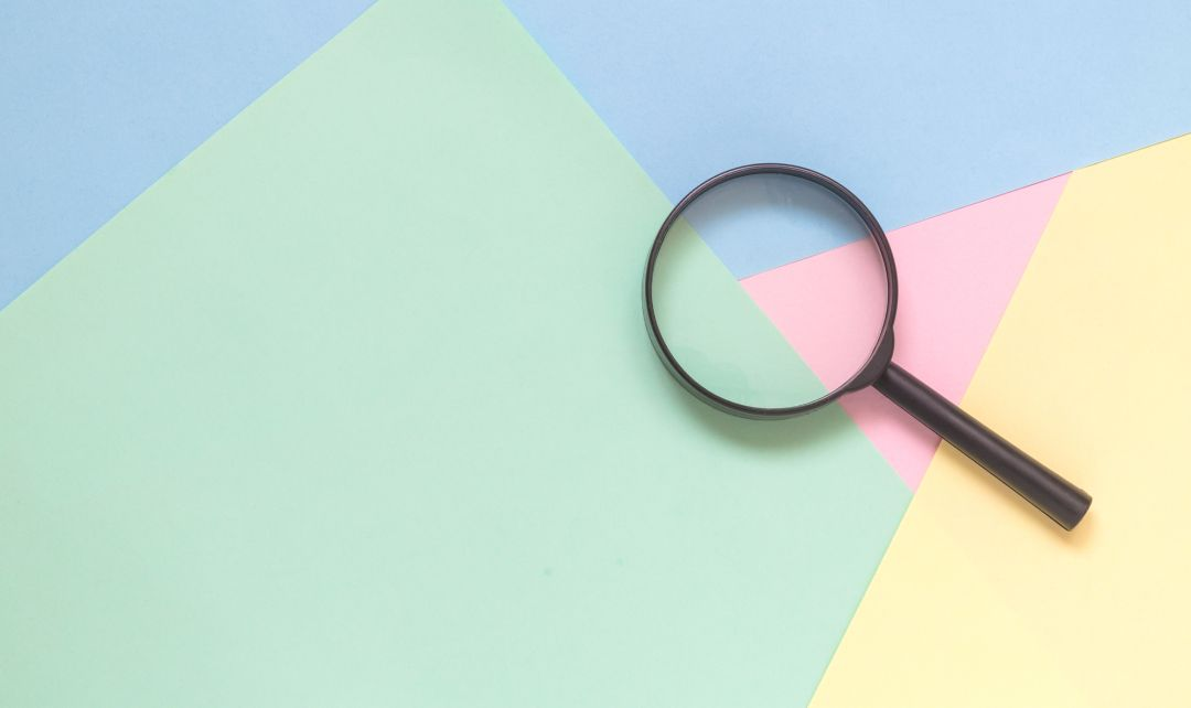 Magnifying glass on a colourful background