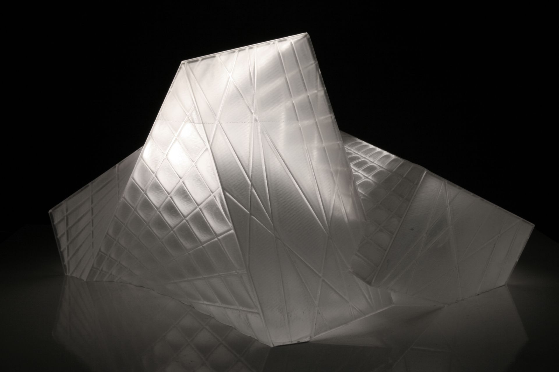This crystalline envelope shelters the visitor without cutting him or her off from the surrounding landscape. As a mental space for prayer rather than an isolated enclosure, the landscape is of essential atmospheric importance and is invited to interact with the building's interior. The technological functions necessary for a modern theatre are submerged in the ground so that the stage can be used flexibly for a range of purposes.