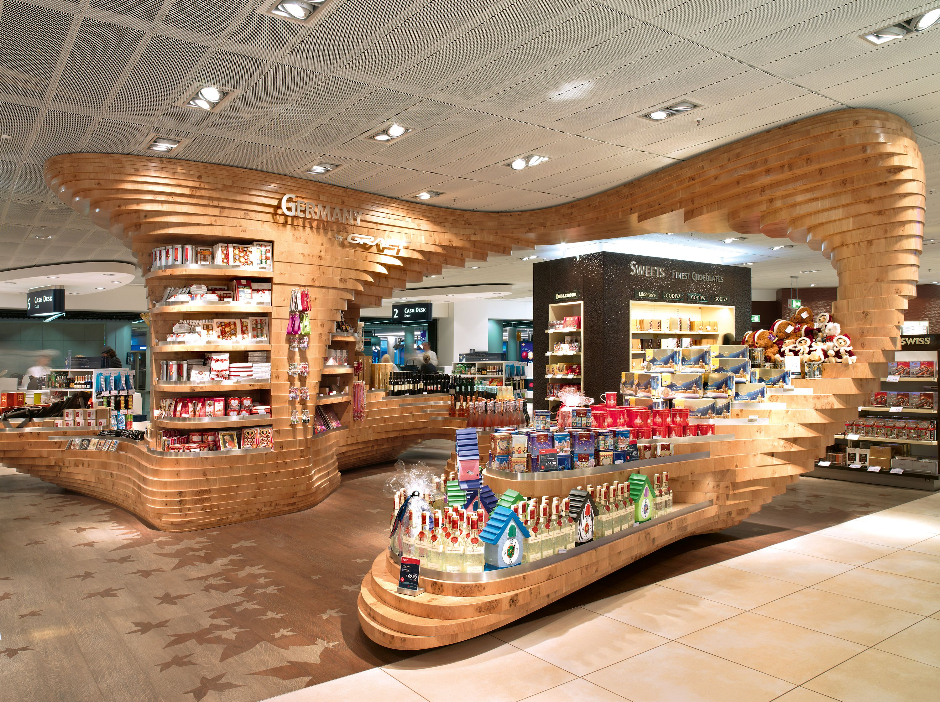 """GRAFT designed forest-themed installations for the """"Made in Germany"""" regional specialty areas of three different Heinemann duty free shops: Dynamic tree sculptures made of stacked layers of oak that serve as eye-catching centerpieces for shoppers."""