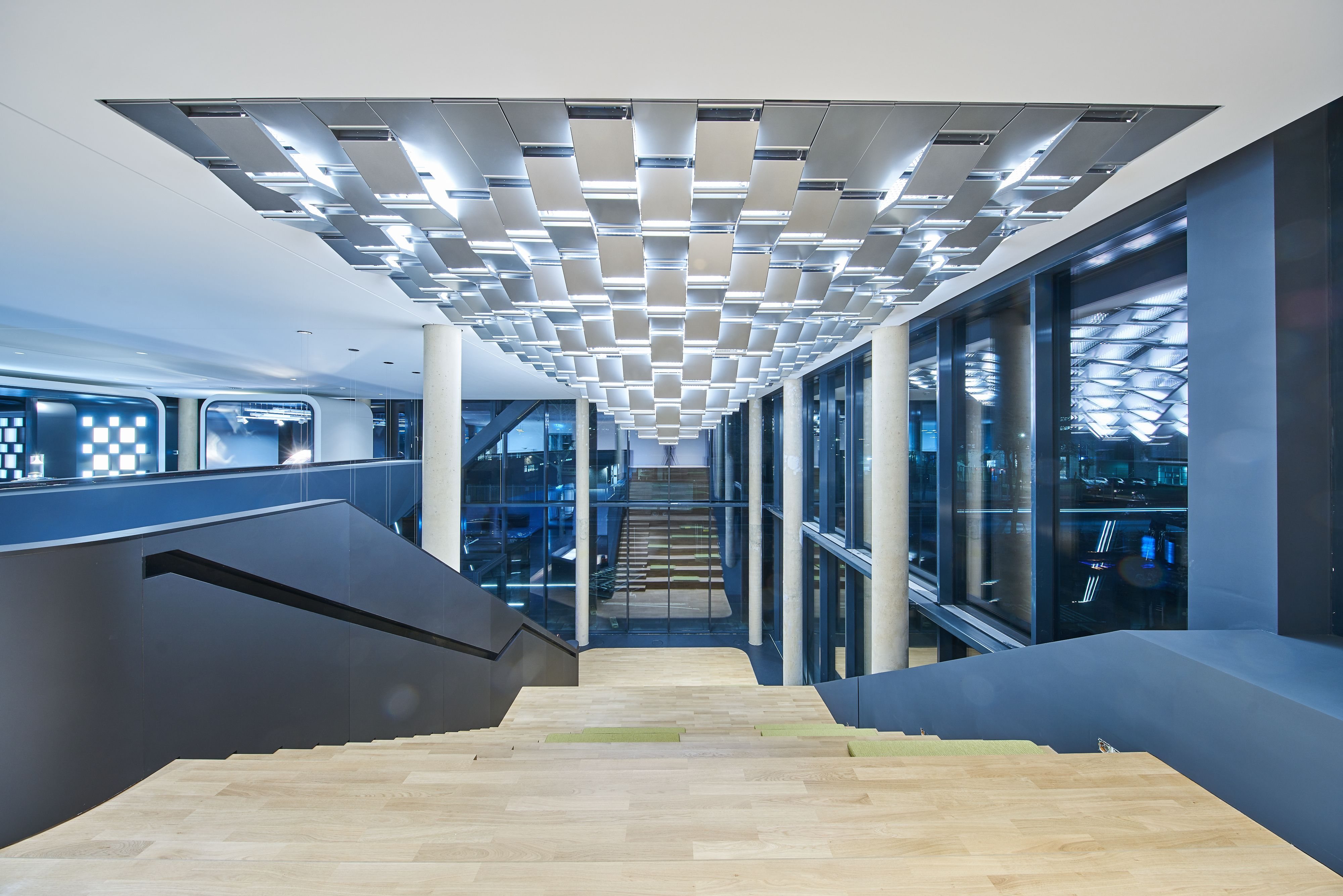TRILUX LIGHT CAMPUS Project type: Office Building     Location: Cologne, Germany     Client: Trilux GmbH & Co KG     Time: 2017-2019     Size: 2,794m2     Photos: Trilux  GRAFT designed the new campus of the German lighting company TRILUX in Cologne. The design of the rectangular building is strongly inspired by the client's craft: light, refraction and reflections are reflected – in the truest sense of the word – throughout the building and its design embodies the precision of lamp manufacture. The continuous, staggered glass façade presents a changing pattern of reflections from different viewpoints and draws inspiration from the aesthetics of spotlight reflectors, which optimize the optical distribution of the light source. To achieve this, each façade module is rotated at the same angle about its central axis. The overall impression is of a monolithic building that produces different light and depth effects depending on the point of view.