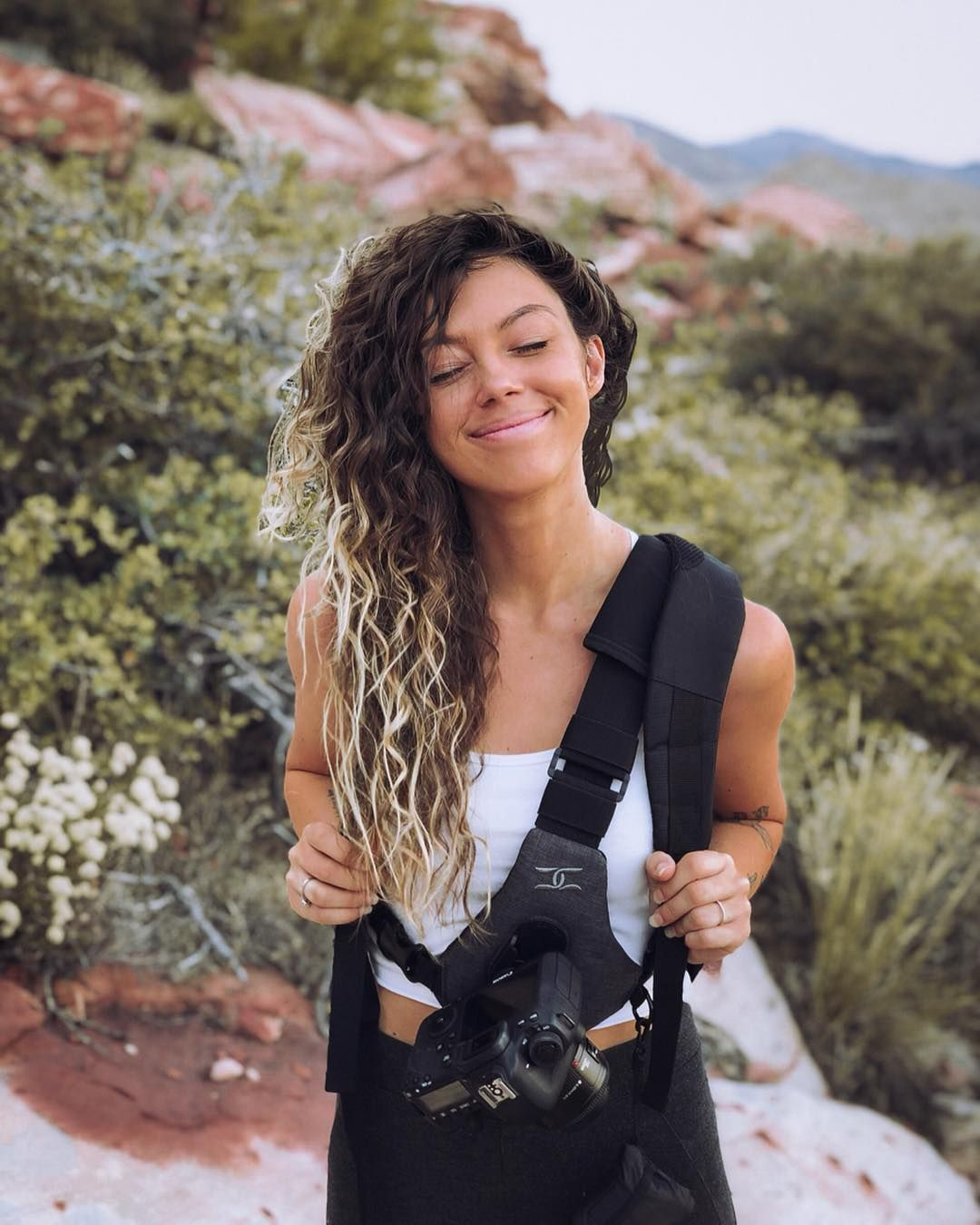 Young person with a camera smiling outdoors