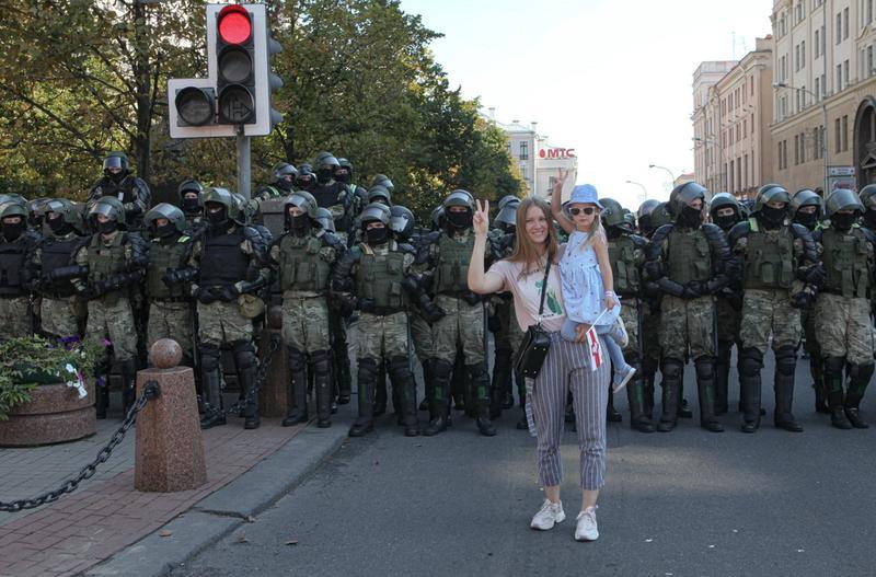 MAKTDEMONSTRASJON: En ung kvinne med et barn på armen viser v-tegnet foran en rad med opprørspoliti i hovedstaden Minsk. Kvinner har fått en fremtredende plass i opprørsbevegelsen, både blant lederskapet og på gatenivå. FOTO: MAXIM SARYCHAU