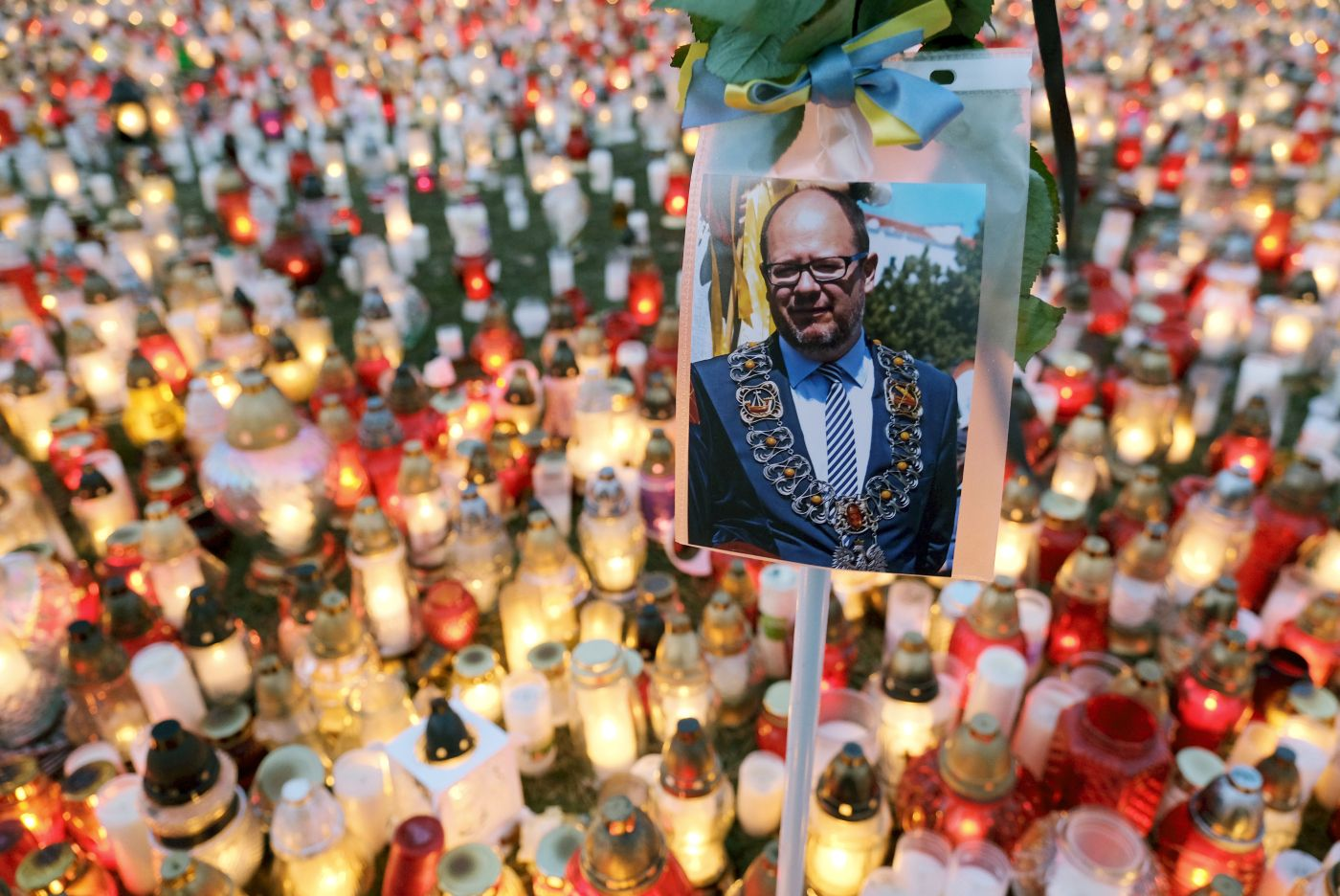 GDANSK, POLAND - JANUARY 17: A photograph of murdered Gdansk mayor Pawel Adamowicz hangs over a sea of candles left by mourners on January 17, 2019 in Gdansk, Poland. Adamowicz was stabbed on stage while attending a charity event in Gdansk last Sunday and died a day later of his injuries. The suspect is a 27-year-old man with a criminal record who was taken into custody. The coffin carrying Adamowicz's body is to be displayed in the European Solidarity Centre later today, where the public may come to pay last respects. Adamowicz's funeral is scheduled for Saturday.  (Photo by Sean Gallup/Getty Images)