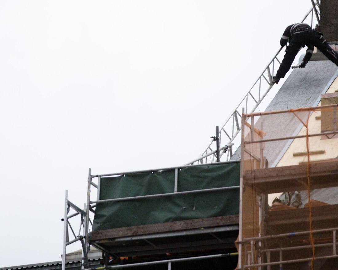 En mann legger kobber på et tak i Oslo sentrum, uten sikring. Arbeidsmiljø, byggebransjen, håndverk, taktekker, taktekking, stillas.      Foto: Tom Henning Bratlie/Klassekampen