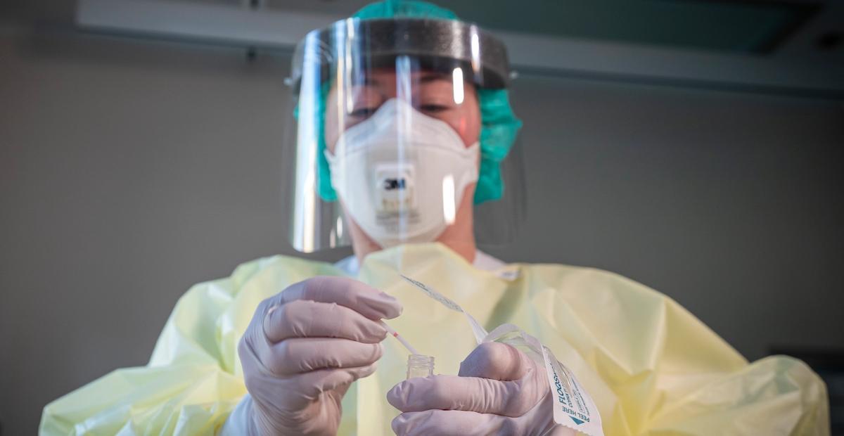 Fagutviklingssykepleier Marte Rygh Selmer ikledd smittevernutstyr med en spyttprøve på isolatposten på Ullevål sykehus. Foto: Heiko Junge,NTB scanpix