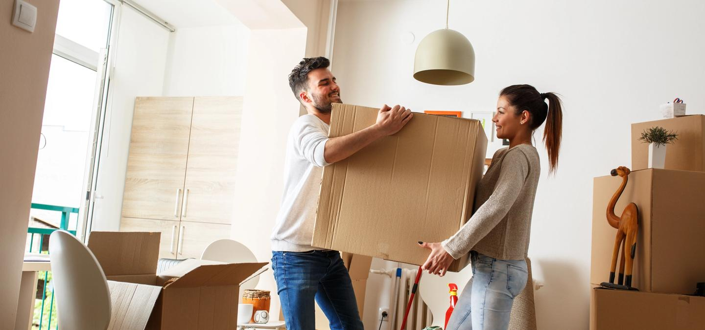 man and woman carrying a moving box
