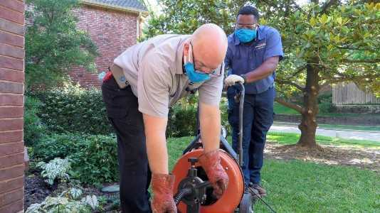 Two Tempo Air plumbers cleaning drain