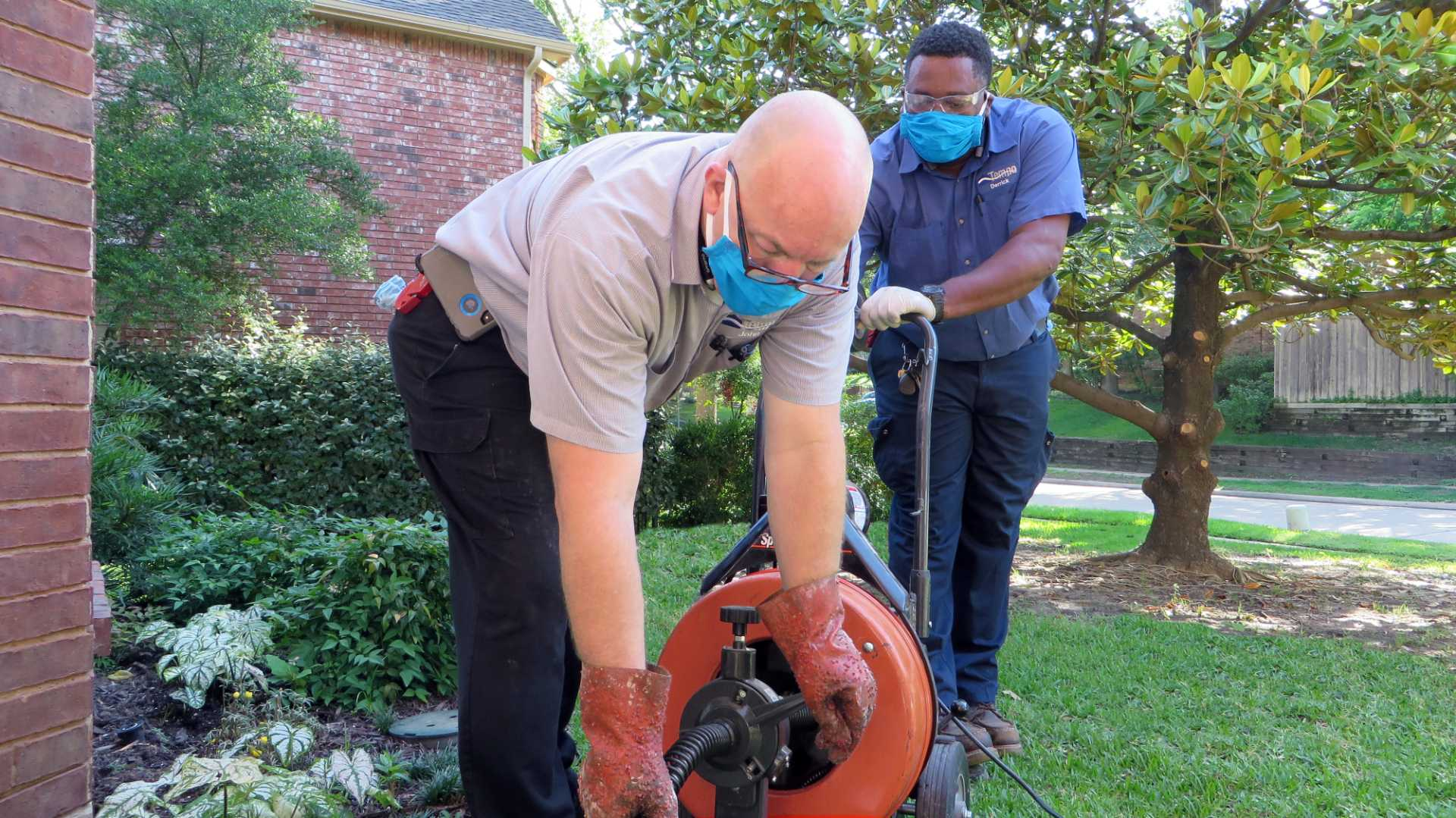 Two Tempo plumbers cleaning drain