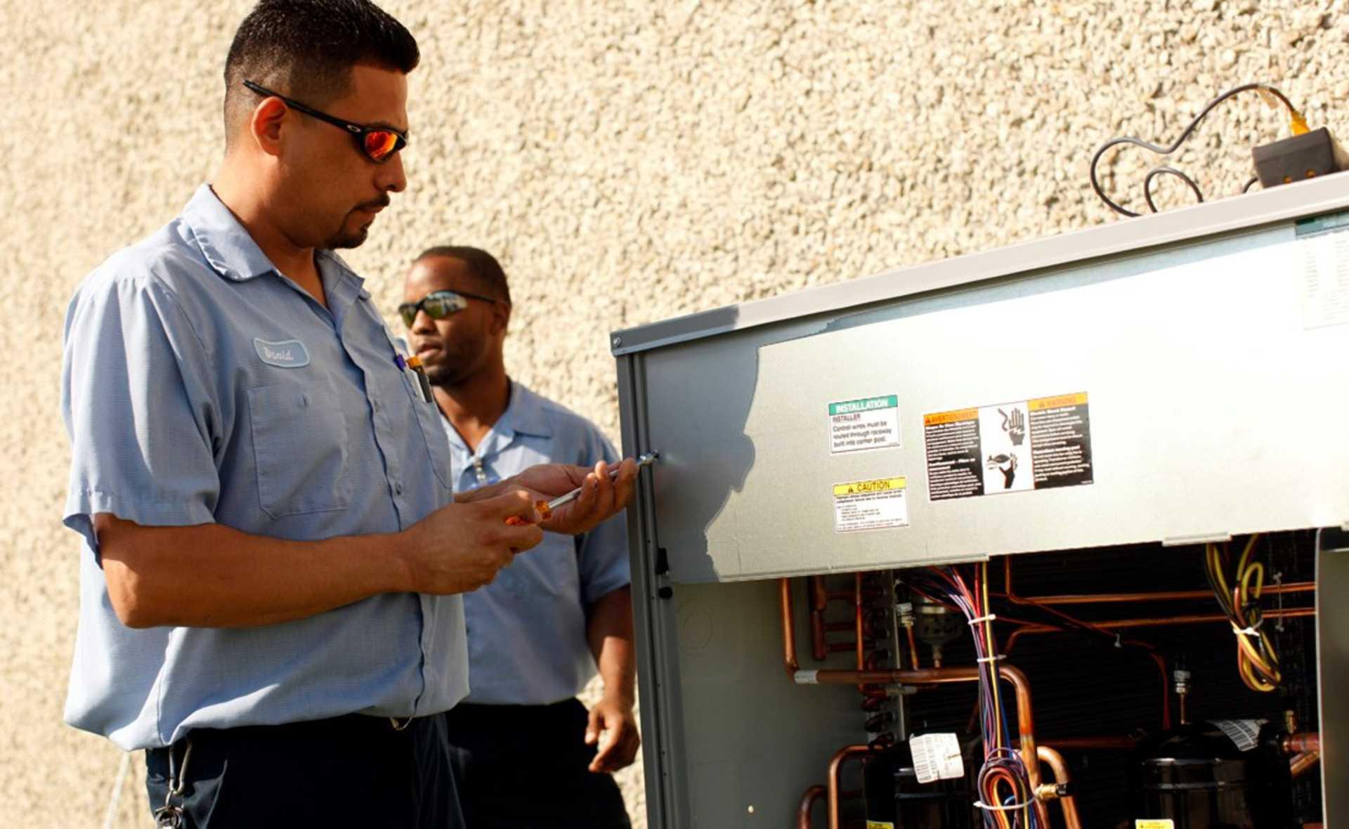 Two HVAC technicians repairing AC unit