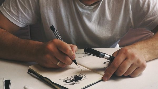 Person drawing at desk