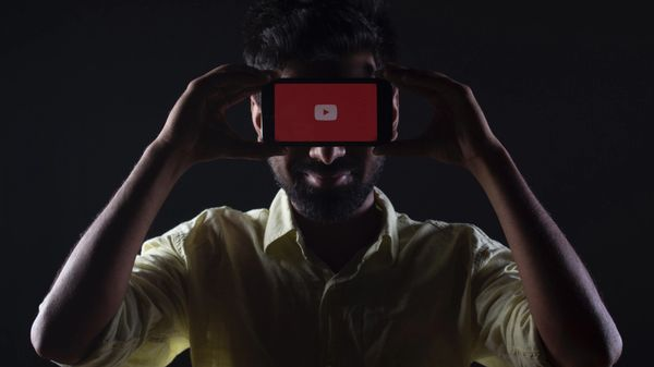 Man holding smartphone with YouTube logo