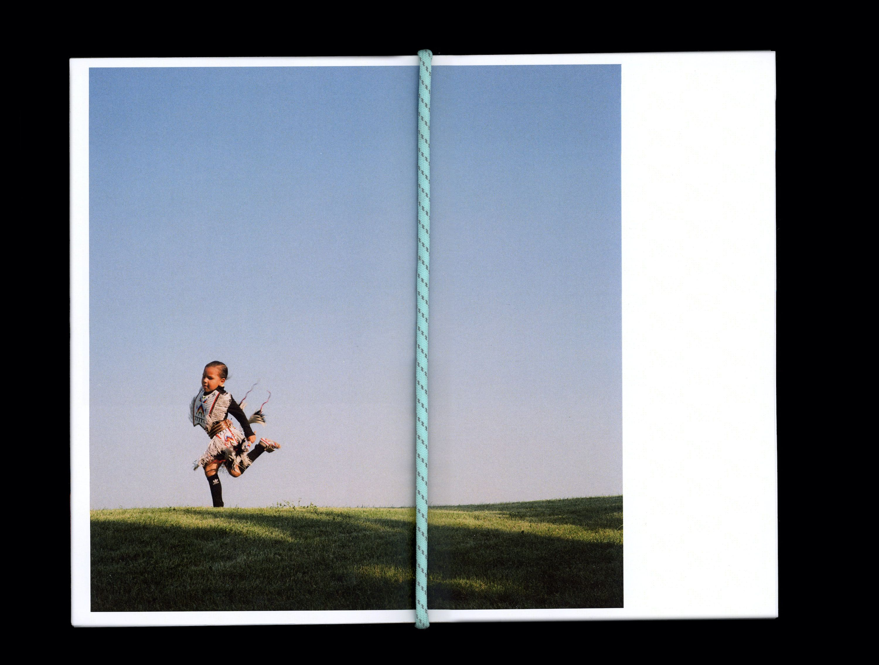 Photograph in book of Tokala Little Sky dancing on grass field with blue sky in the background