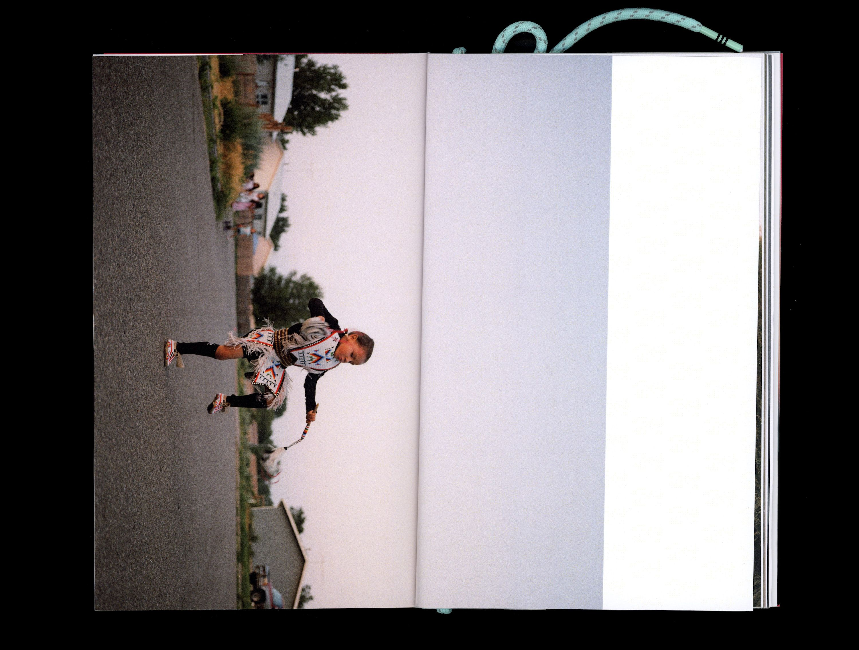 Photograph in book of Tokala Little Sky dancing in road wearing traditional Native clothing