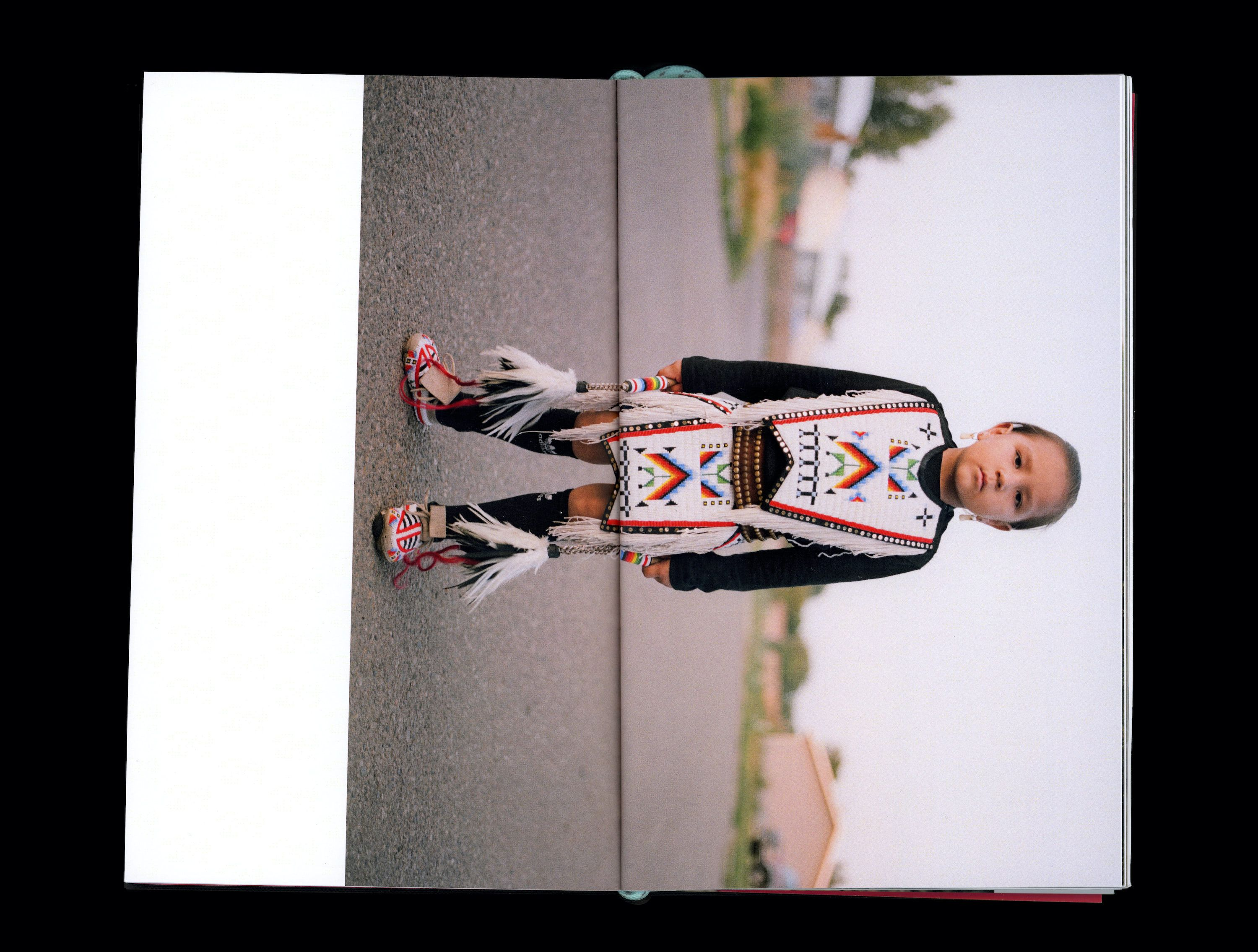 Photograph in book of Tokala Little Sky standing on asphalt road wearing traditional Native clothing