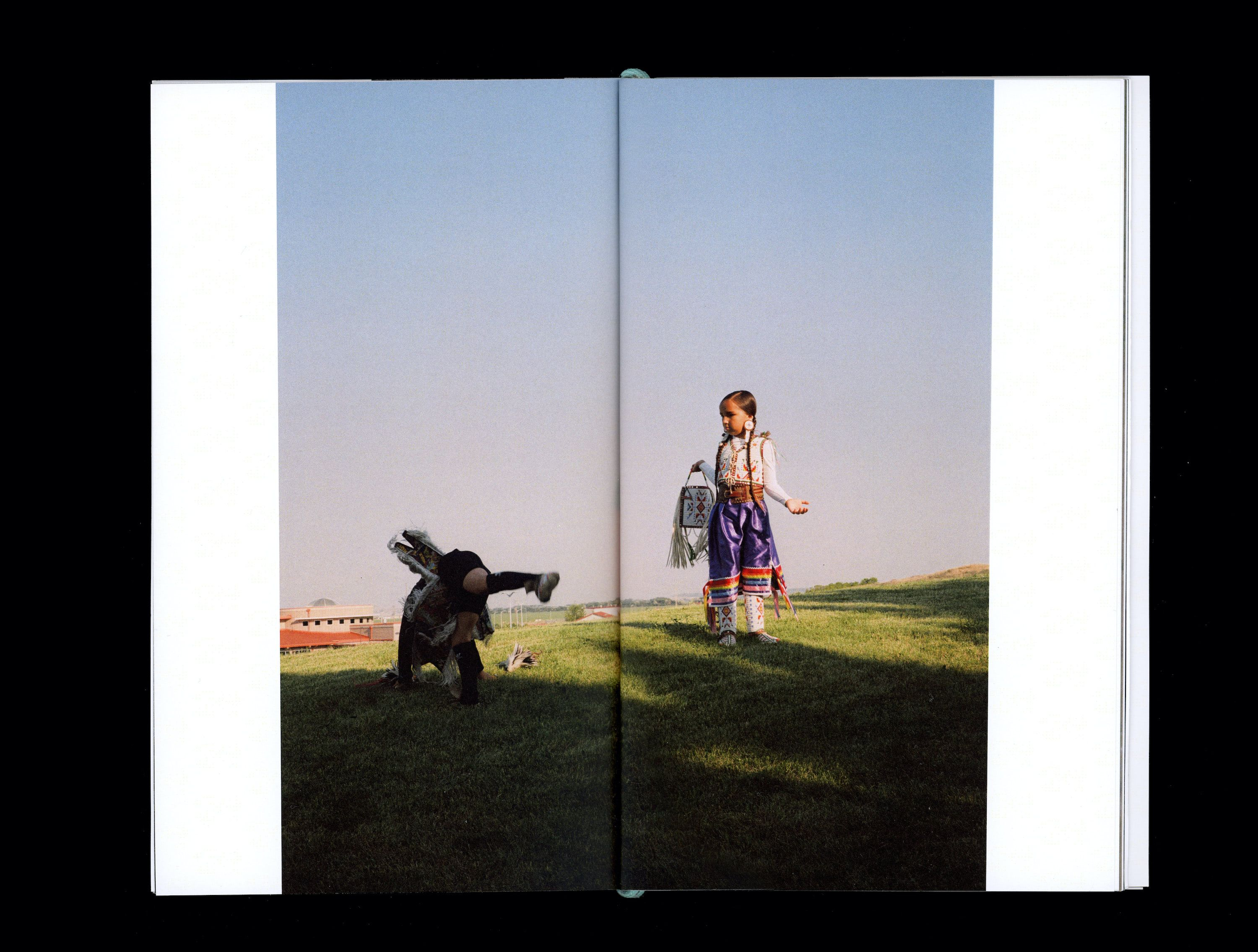 Photograph in book of Tokala & Ataya Little Sky playing on grassy hill