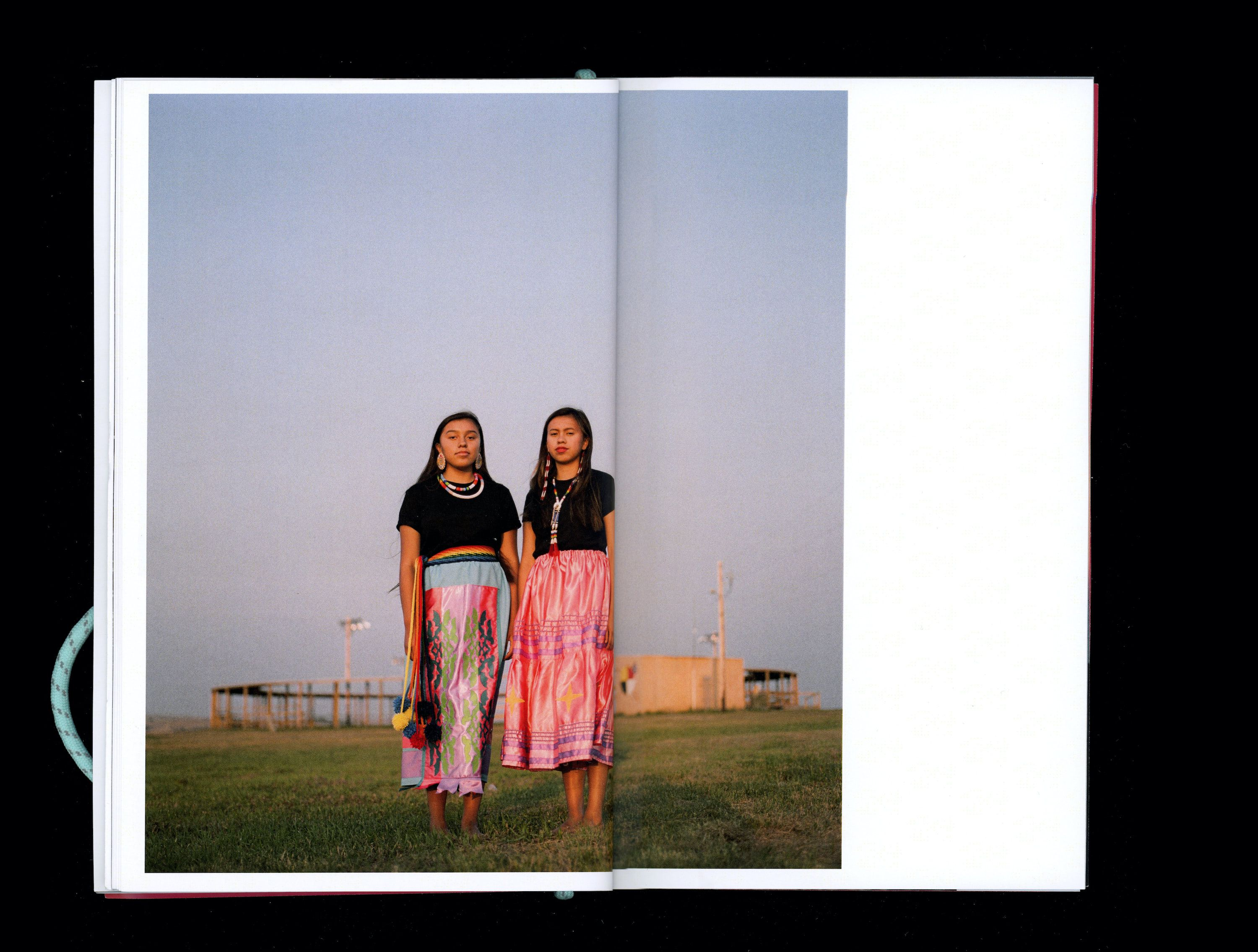 Photograph in book of Jonna & ToiRee Brady wearing colourful native clothing standing on grass field