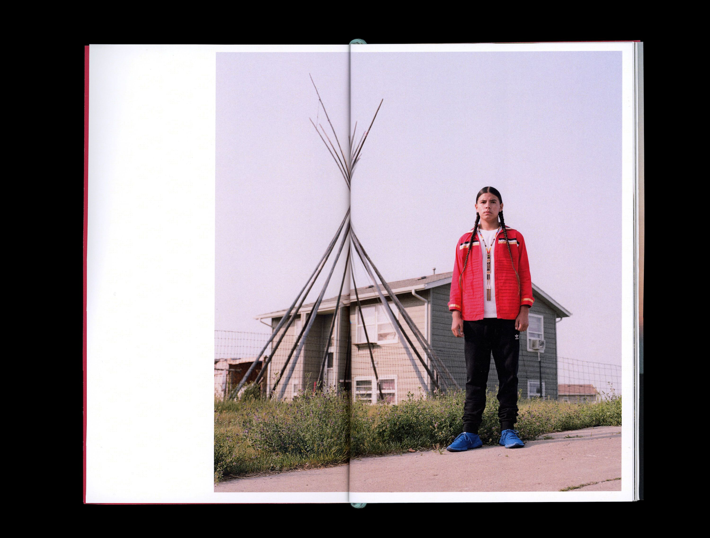 Photograph in book of Zaniyan Iron Eyes standing in front of house and teepee frame