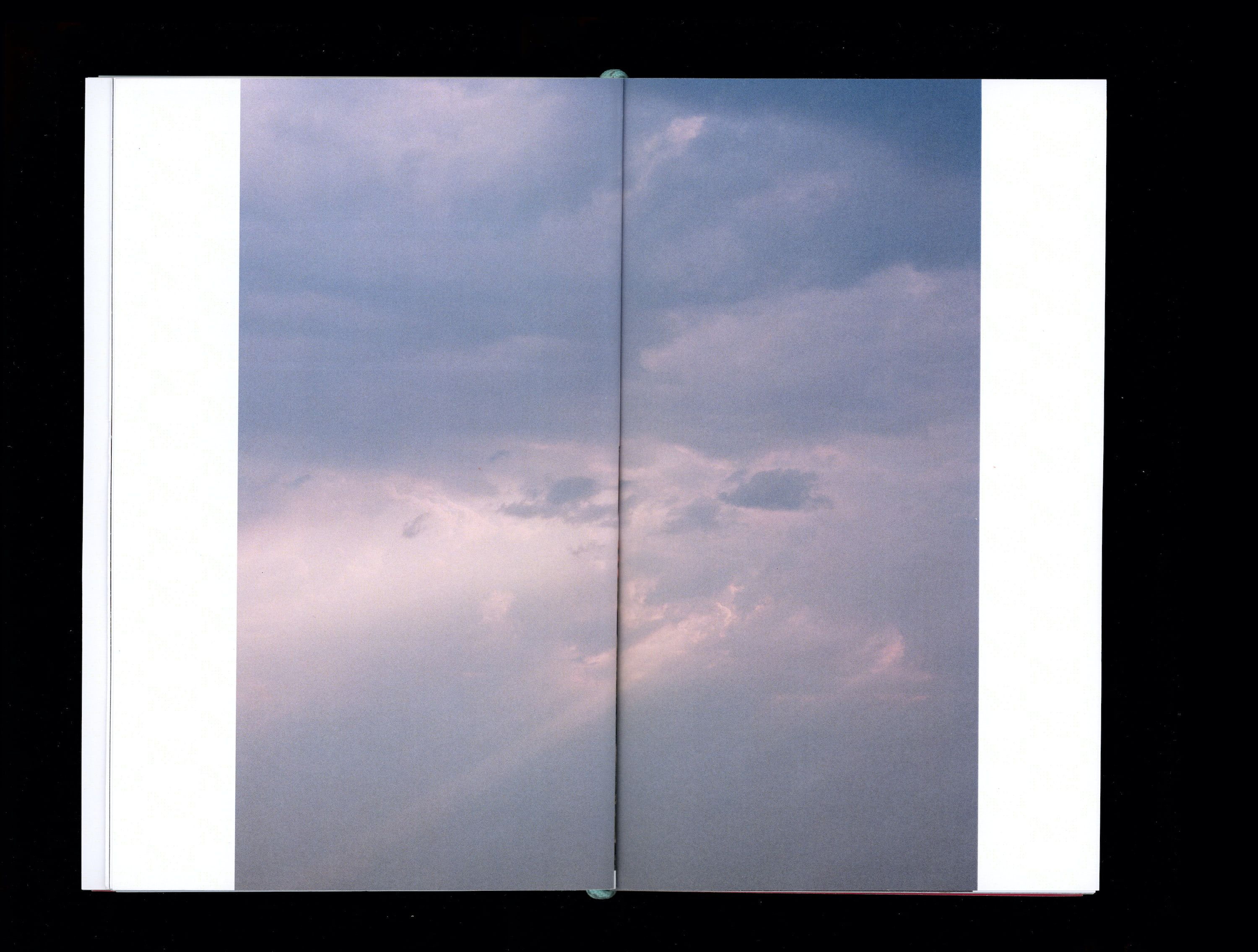 Photograph in book of grey clouds with pink sunlight shining through